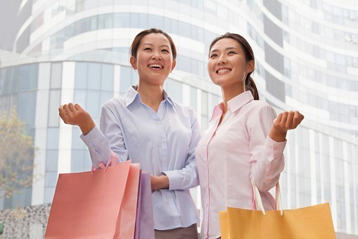 Smiling Chinese businesswomen carrying shopping bags : Stock Photo