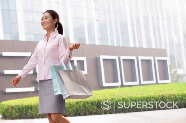 Smiling Chinese businesswoman carrying shopping bags : Stock Photo