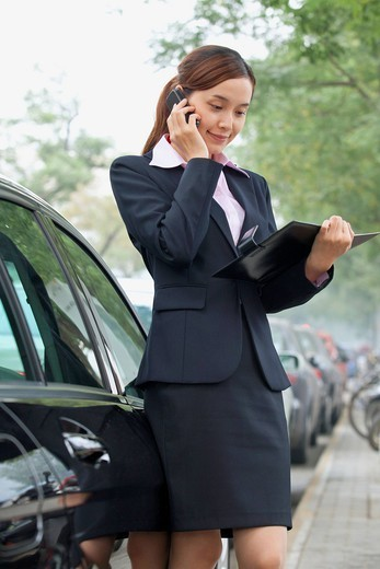 Chinese businesswoman looking at notebook and talking on cell phone : Stock Photo