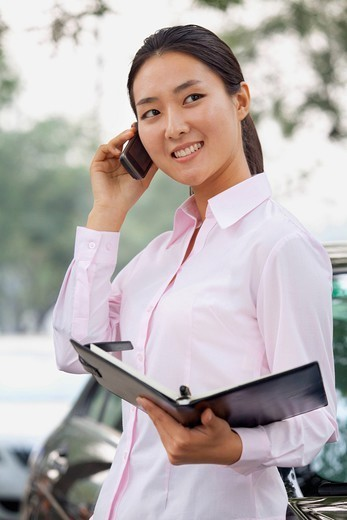 Chinese businesswoman holding notebook and talking on cell phone : Stock Photo
