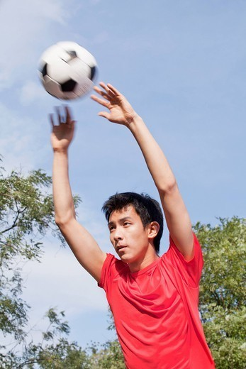 Chinese man playing soccer : Stock Photo
