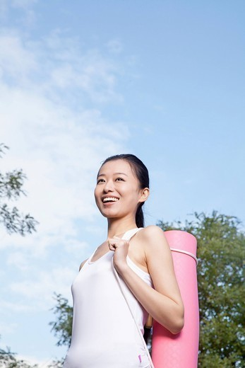 Chinese woman carrying yoga mat : Stock Photo