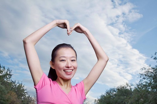 Chinese woman with arms raised making heart_shape : Stock Photo