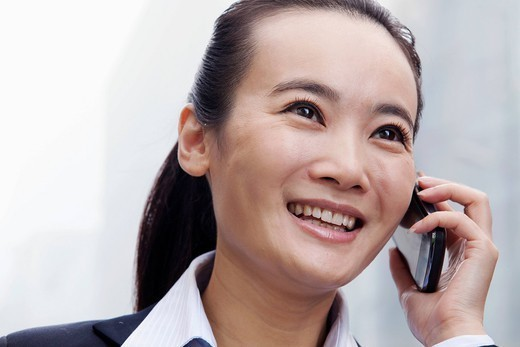 Smiling Chinese businesswoman talking on cell phone : Stock Photo