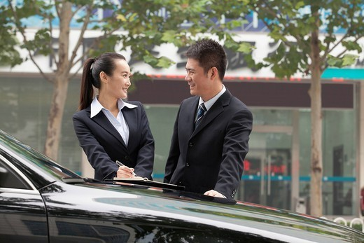 Chinese business people standing near car working : Stock Photo