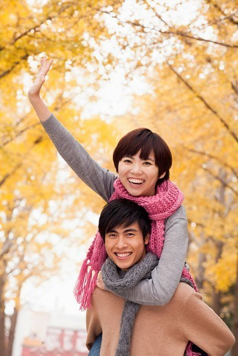 Chinese man giving girlfriend piggy back ride : Stock Photo