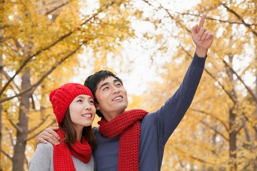 Chinese man showing something to girlfriend : Stock Photo