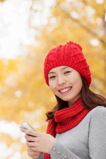 Chinese woman text messaging on cell phone : Stock Photo