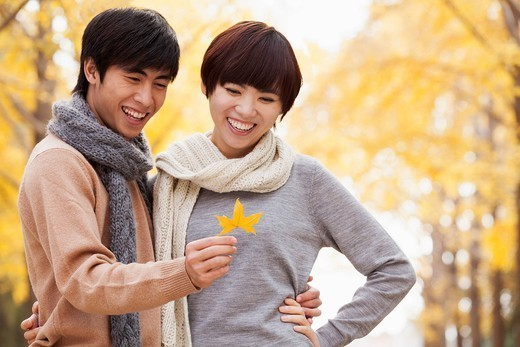 Chinese couple looking at autumn leaf : Stock Photo
