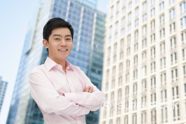 Smiling Chinese man with arms crossed : Stock Photo