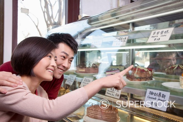 Stock Photo: 1589R-170161 Chinese couple looking at cake in display case