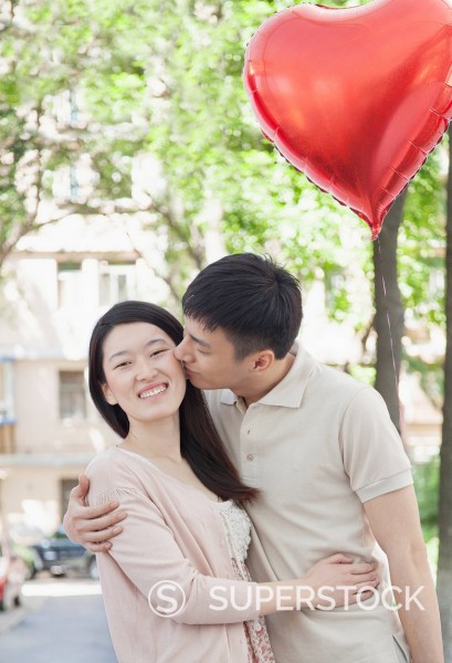 Chinese man kissing girlfriend on Valentine´s day : Stock Photo