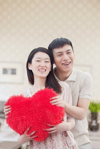 Chinese couple holding Valentine pillow : Stock Photo