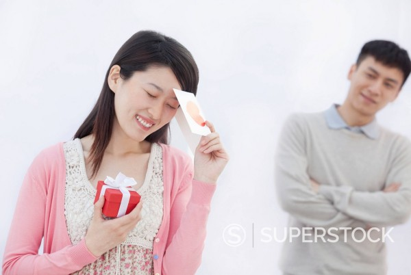 Stock Photo: 1589R-170178 Chinese woman holding Valentine card and holding gift