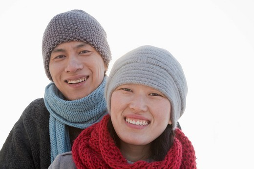 Smiling Chinese couple wearing scarves and caps : Stock Photo