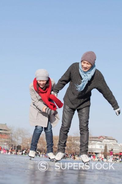 Chinese couple ice skating : Stock Photo