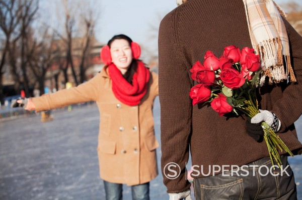 Chinese boyfriend holding flowers for ice skating girlfriend : Stock Photo