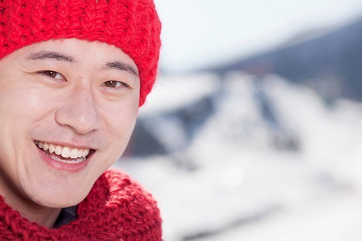 Smiling Chinese man in red scarf and cap : Stock Photo
