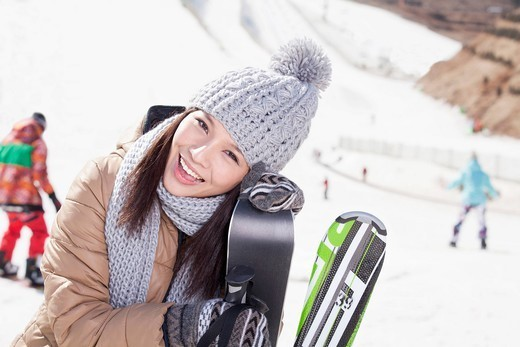 Chinese woman standing on ski slope with skis : Stock Photo