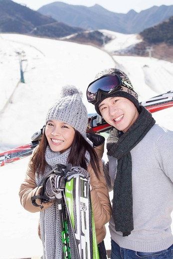 Stock Photo: 1589R-170239 Chinese couple standing on ski slope with skis
