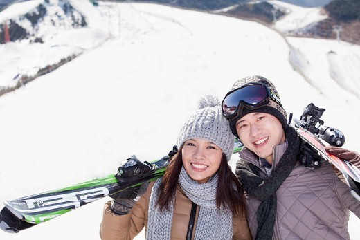 Stock Photo: 1589R-170241 Chinese couple standing on ski slope with skis