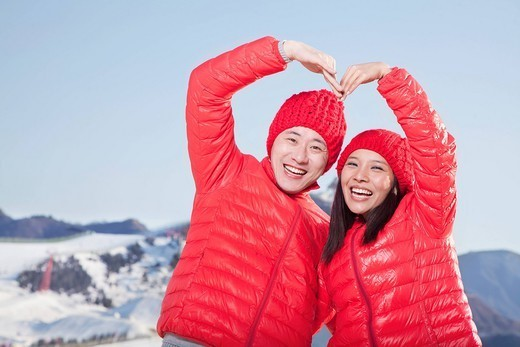 Chinese couple making heart_shape gesture : Stock Photo