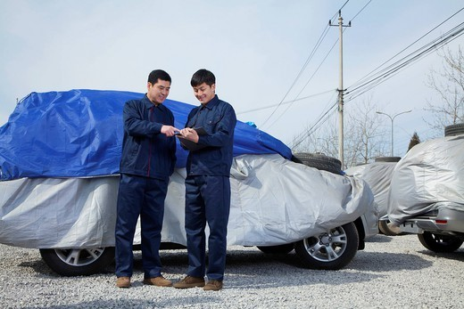 Chinese men standing next to covered car : Stock Photo