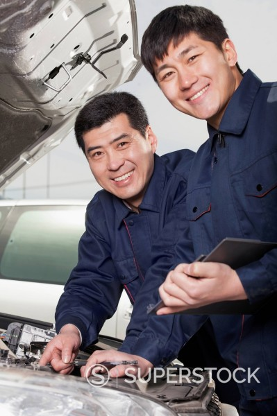 Chinese men looking underneath hood of car : Stock Photo