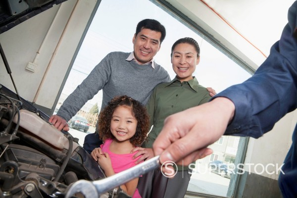 Stock Photo: 1589R-170332 Chinese family watching mechanic work on their car