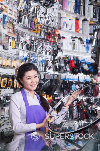 Stock Photo: 1589R-170356 Chinese worker holding wheel in bike shop