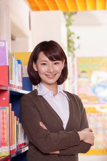 Chinese teacher standing in library : Stock Photo
