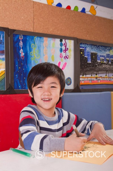 Smiling Chinese boy drawing : Stock Photo