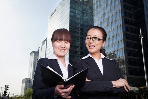 Chinese businesswomen looking at planner : Stock Photo