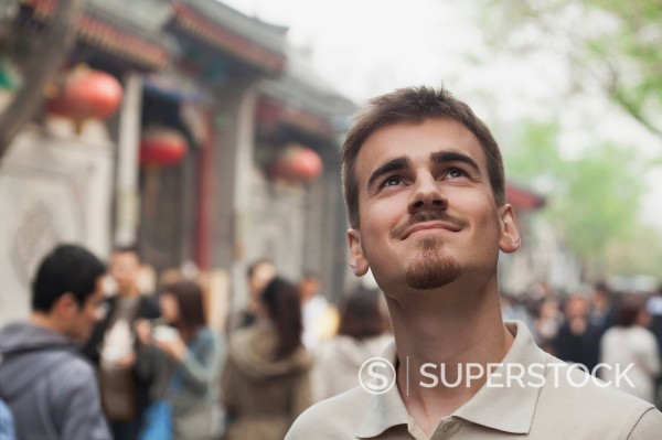 Smiling mixed race man looking up outdoors : Stock Photo