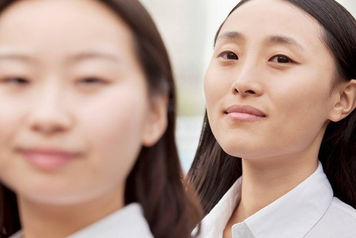 Smiling Chinese businesswomen standing together : Stock Photo