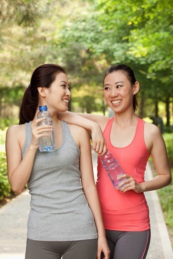 Chinese women drinking water after exercise : Stock Photo
