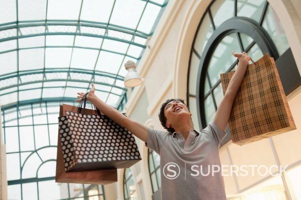 Stock Photo: 1589R-170555 Chinese man raising shopping bags