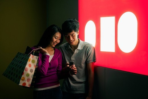 Chinese couple shopping and looking at cell phone : Stock Photo