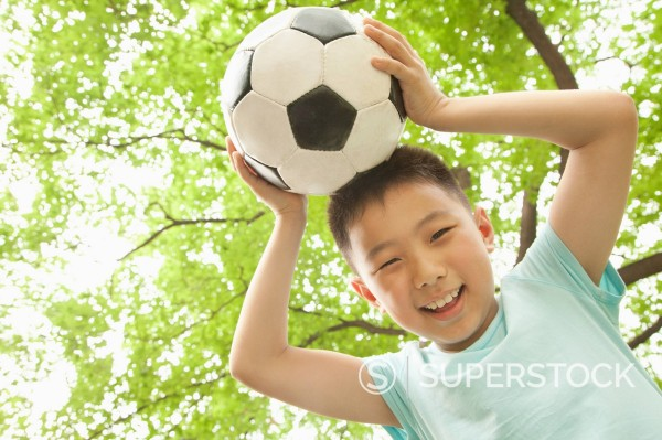 Stock Photo: 1589R-170592 Chinese boy holding soccer ball on head
