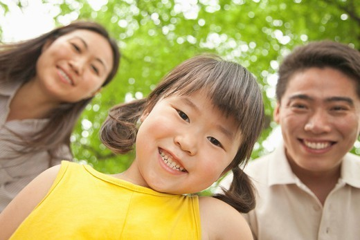 Chinese family smiling in park : Stock Photo