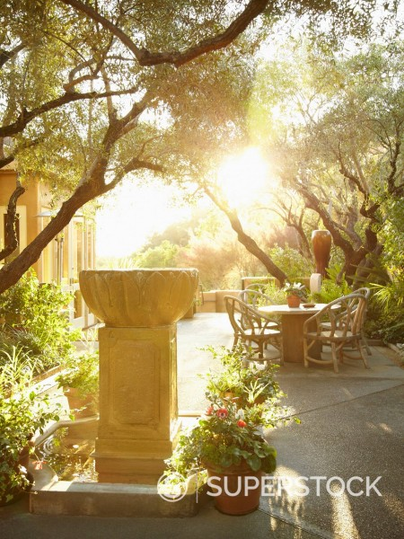 Stock Photo: 1589R-171179 Sunflare coming through outdoor patio area in nature with fountain in foreground