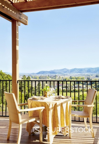 Stock Photo: 1589R-171182 Private dining table and chairs on a restaurant deck overlooking wine country at a luxury resort in Napa Valley, California