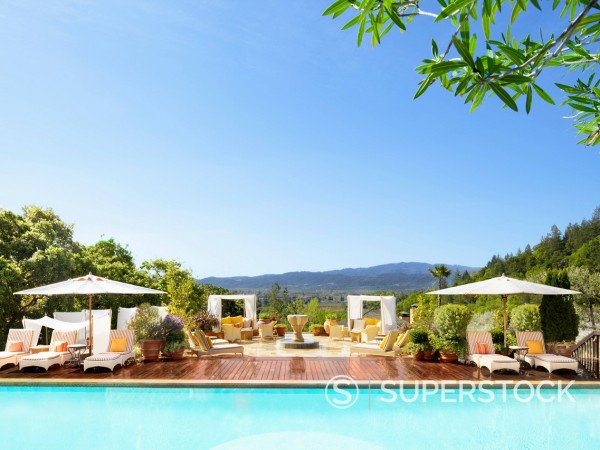Stock Photo: 1589R-171186 Swimming pool with striped chaise lounge chairs and umbrellas at a luxury resort overlooking Napa Valley, California
