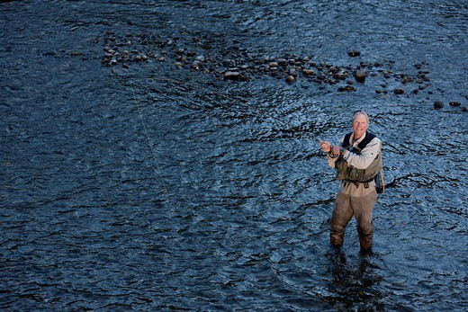 Caucasian man fly_fishing in river : Stock Photo
