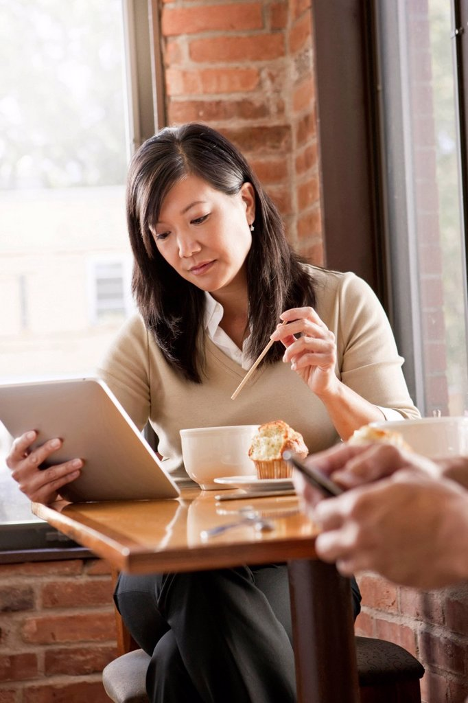 Stock Photo: 1589R-171202 Chinese woman using digital tablet in cafe