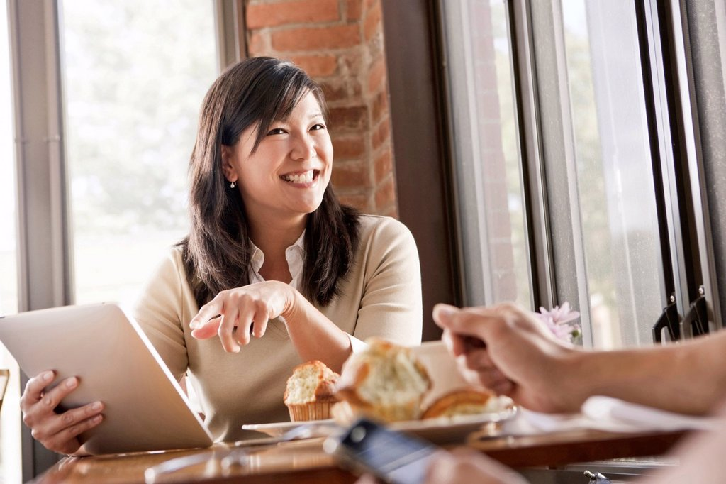 Chinese woman using digital tablet in cafe : Stock Photo