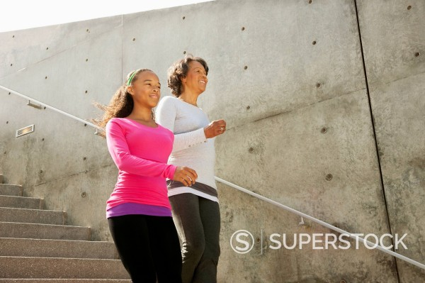 Grandmother and granddaughter running down urban steps : Stock Photo