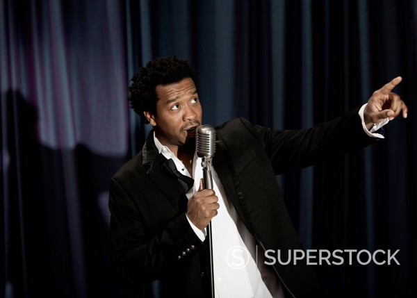 Black singer in tuxedo holding microphone : Stock Photo