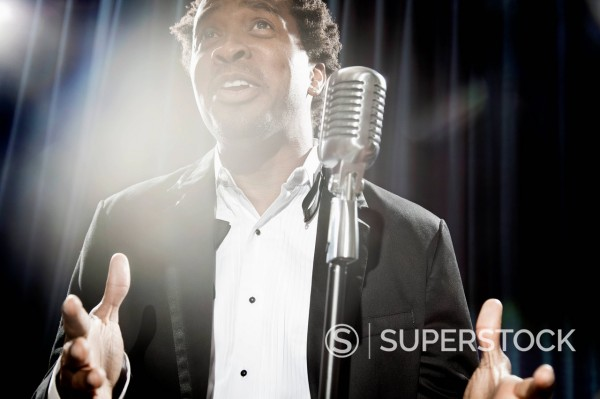 Stock Photo: 1589R-171240 Smiling Black man in tuxedo standing at microphone