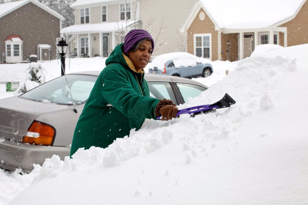 African American woman scraping snow from windshield : Stock Photo